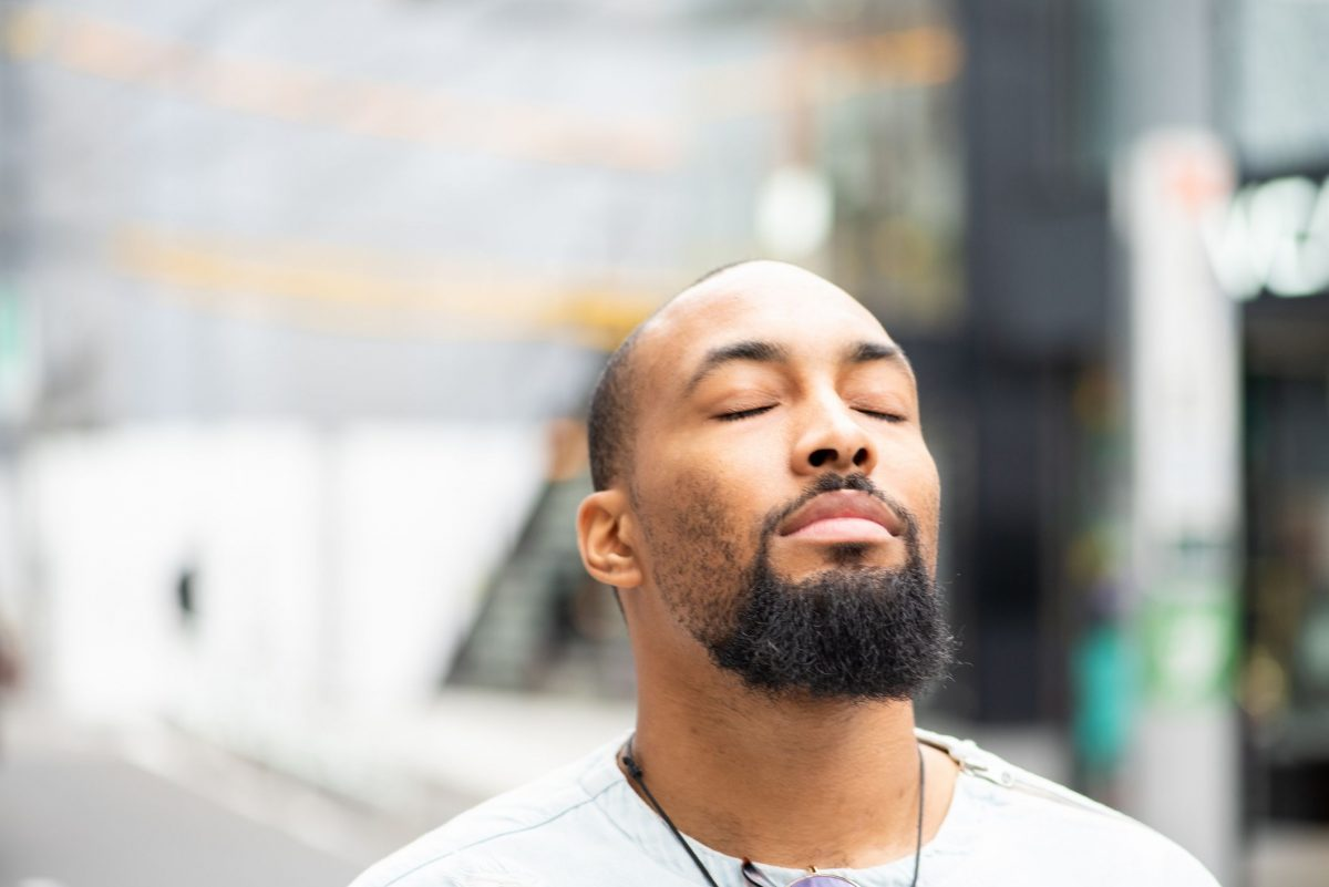 Man with beard and white shirt taking a deep breath